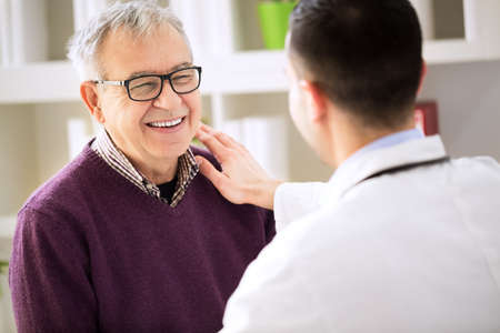 Smiling happy old patient visit doctor Stock Photo