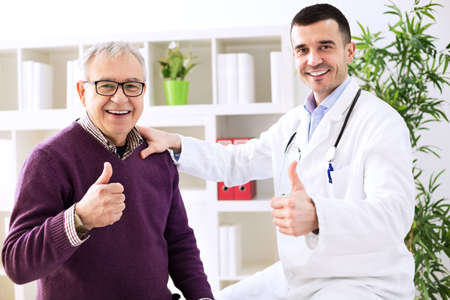 Doctor specialist and healthy patient shows finger up 스톡 콘텐츠