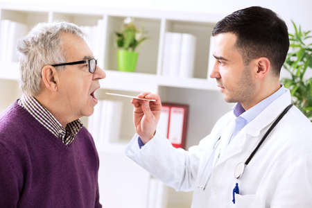 Doctor examining old patient sick throat