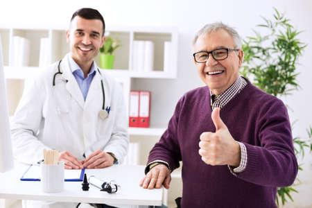 uomo felice: Soddisfatto vecchio paziente con successo giovane medico in ufficio Archivio Fotografico