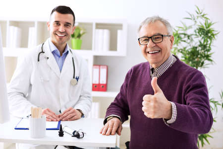Satisfied old patient with success young doctor in office Stockfoto