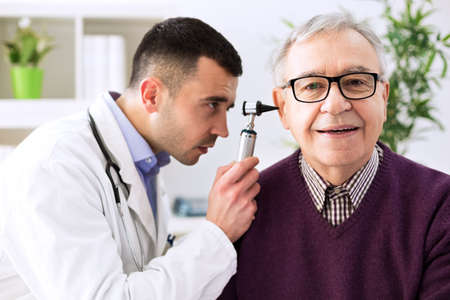 Doctor holding otoscope and examining senior patient ear