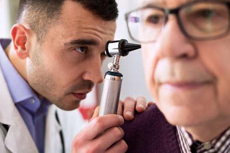 otoscope: Otologist examining senior patient ear