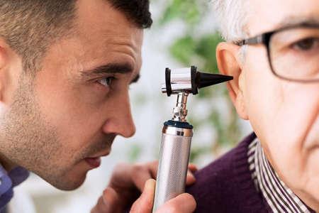 otologist: Otologist looking through otoscope and exam patient ear