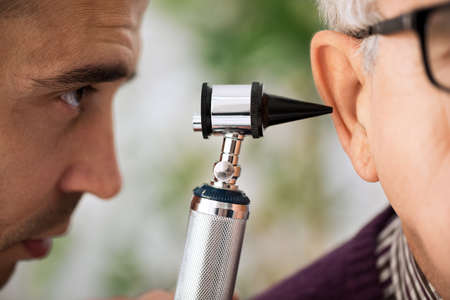 otologist: Doctor specialist Performs an Ear Examination close up Stock Photo