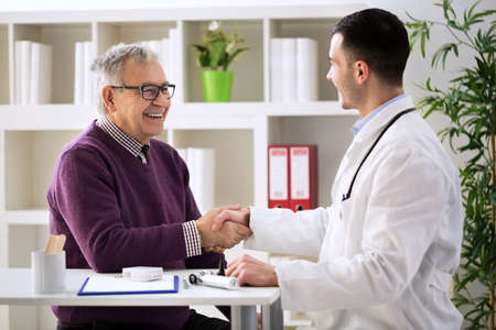 Young doctor congratulating senior patient on recovery Stockfoto