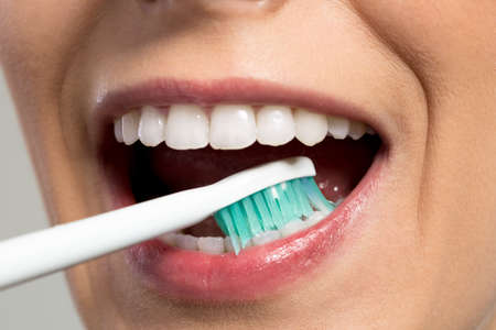 after: Girl rubbing teeth with toothbrush close up