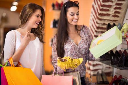 comprando zapatos: Mujeres que compran zapatos de verano en una tienda