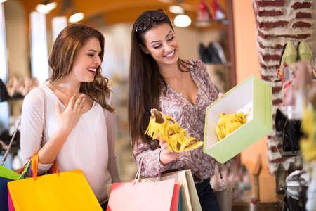 comprando zapatos: Mujer sonriente que muestra a su amiga perfecta sandalias de verano