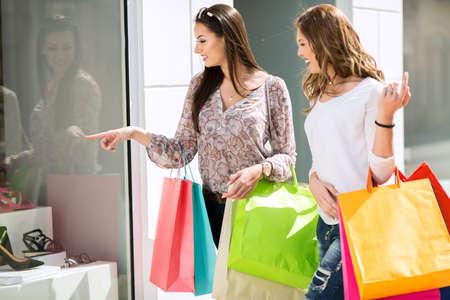 comprando zapatos: Las mujeres jóvenes en el centro comercial mirando footwearshoes Foto de archivo