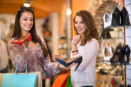 comprando zapatos: Mujeres Felices compra de zapatos en una tienda