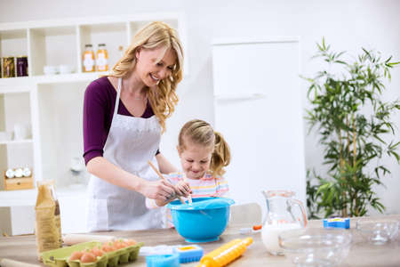 family together: Beautiful woman and girl making homemade cookies