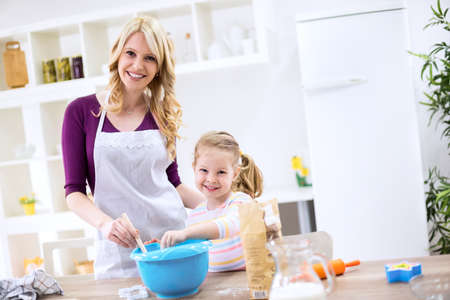 Smiling happy child and mother cooking together