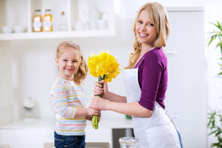 Happy mother and daughter with flowers for mothers day