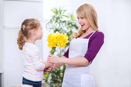 donates: Cute daughter donates mother a bouquet of flowers for mothers day