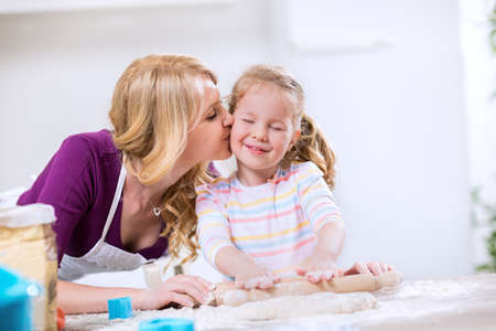 kiss biscuits: Lovely mother kissing worth daughter, making cookies together