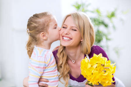 family mart: Beautiful daughter giving flowers and kiss to smiling happy mohter Stock Photo
