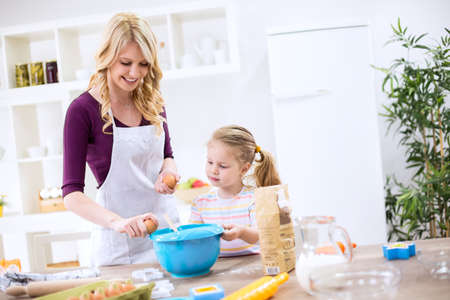 Young mother teaching child how to make dough Stock Photo
