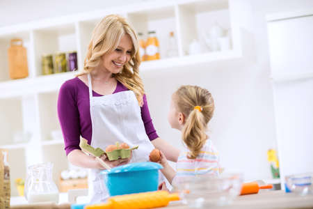 Woman giving egg to daughter to make pancakes Stock Photo