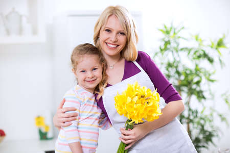 family mart: Child and mother in the embrace with flowers for mothers day Stock Photo