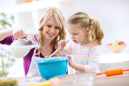 children eating: Beautiful mother and daughter baking pancakes