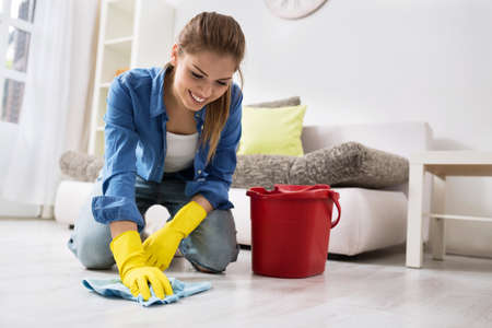 Smiling girl wash the floor with rag and detergent Imagens
