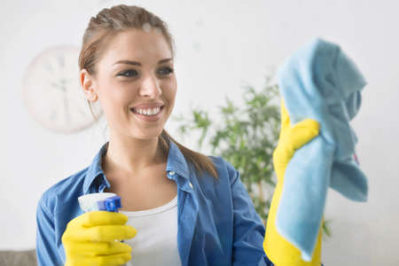 Smiling woman clean the window with rag