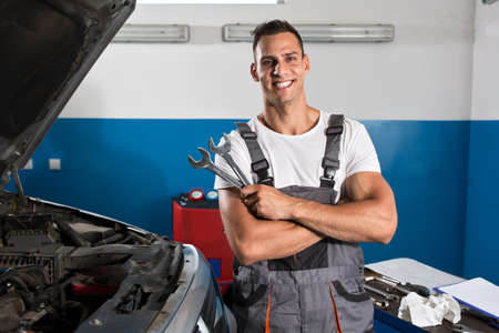 happy worker: Satisfied and happy mechanic holding tools