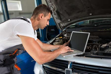malfunction: Mechanic using laptop to diagnostic malfunction at car