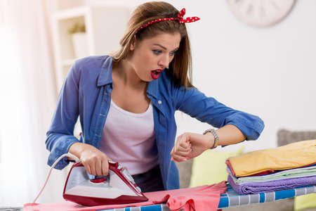 hurry up: Frustated woman ironing laundry hurry up and looking at her watch