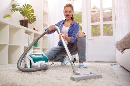 personal de limpieza: Joven y bella mujer de la limpieza con aspiradora en casa