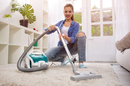 Beautiful young woman cleaning with vacuum cleaner at home
