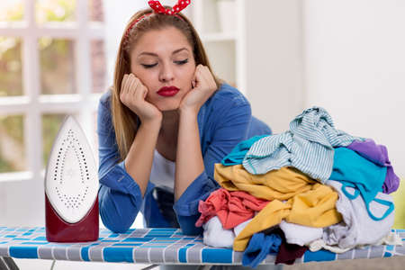 dry cleaner: Lazy young woman looks at laundry on ironing board