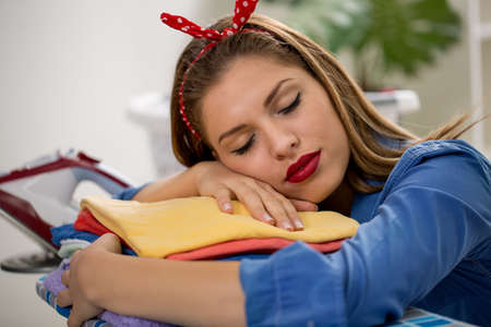 ironed: Tired young woman sleeping on the ironed laundry at home Stock Photo