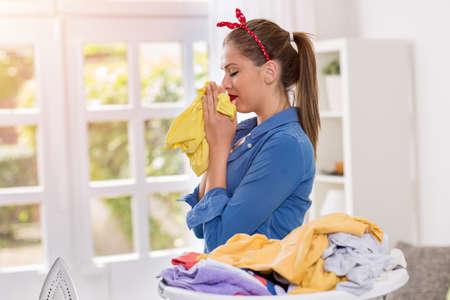 olfato: Un ama de casa joven y bella olor de la ropa recién lavada Foto de archivo