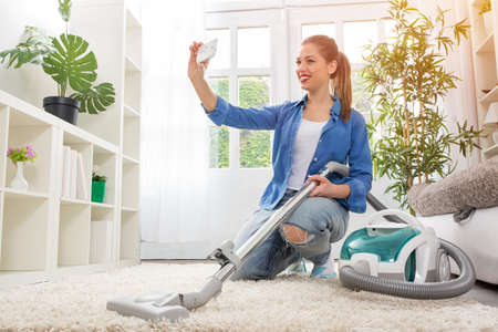 Woman with vacuum cleaner cleaning carpet and taking selfie at home