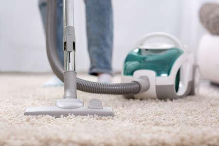家庭で真空掃除機でのカーペットの掃除 写真素材