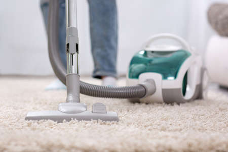 Cleaning carpet with vaccum cleaner at home