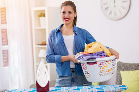 clean clothes: Smiling young woman holding basket with clean clothes