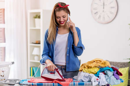 woman ironing: Charming young woman ironing laundry and talking on phone Stock Photo