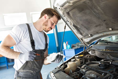 Young professional mechanic checks the oil in a car