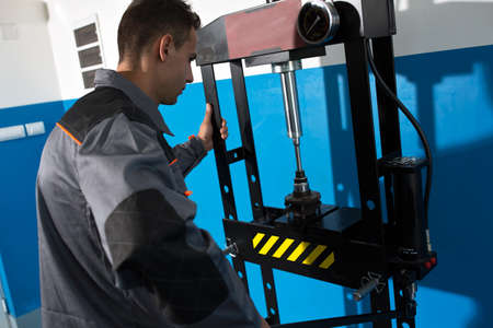 occupied: Occupied mechanic work at the garage on press machine Stock Photo