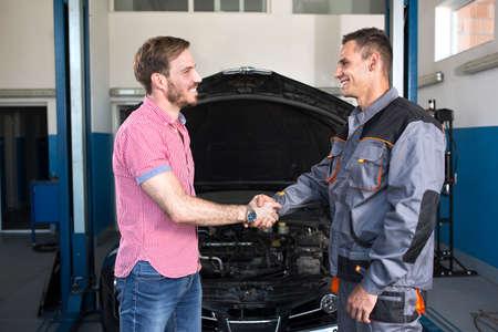 Glimlachende klant en monteur handen schudden bij de autodienst