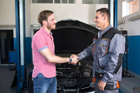 mechanics: Smiling customer and mechanic shaking hands at auto service Stock Photo