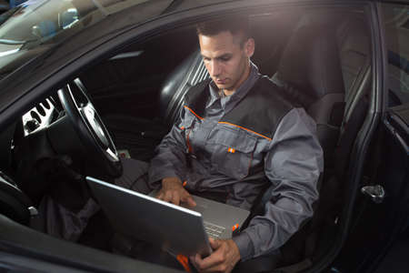 diagnostic tool: Professional car mechanic working in auto repair service, diagnostic time