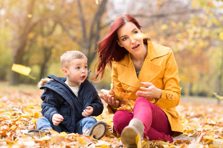female child: Mother and son watching fallen leaves at park