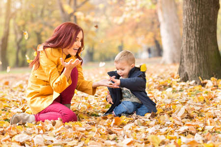 female child: Mother and son in the autumn park Stock Photo