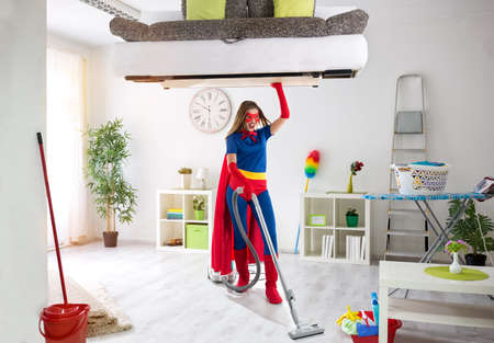 Strong super hero housewife cleaning home and holding bad in the air