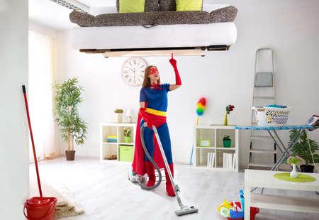 Worth super hero woman in costume use vacuum cleaner, hygiene time