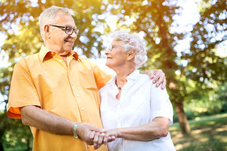 Happy and handsome senior couple hugging in park Stock Photo